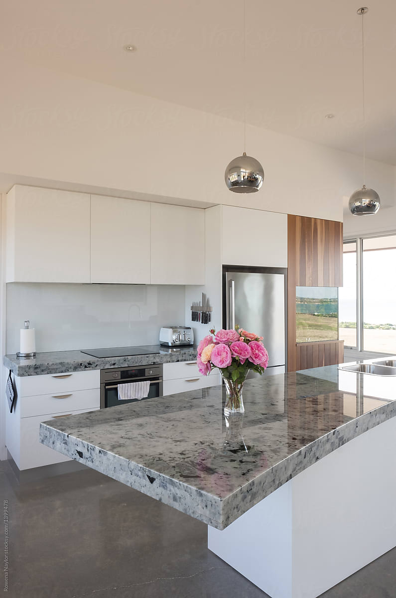 Modern Kitchen With Island Bench And Chrome Pendant Lights By Rowena Naylor Stocksy United