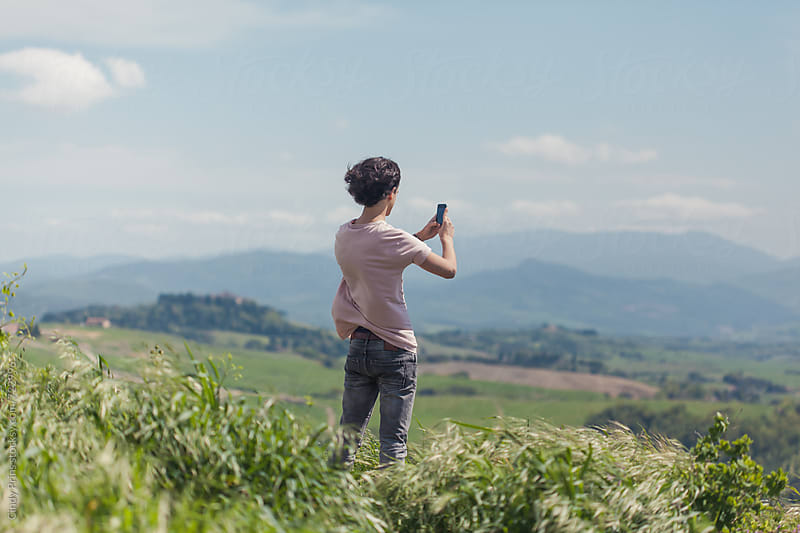 Teenage boy standing in the hills in Tuscany taking a picture with his phone by Cindy Prins for Stocksy United