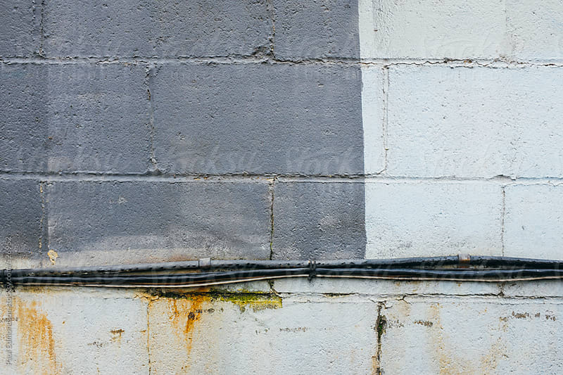 Grey and silver paint covering graffiti on building wall by Paul Edmondson for Stocksy United