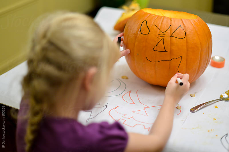 Little Girl Drawing Face on Orange Halloween Jack-O-Lantern by JP Danko for Stocksy United