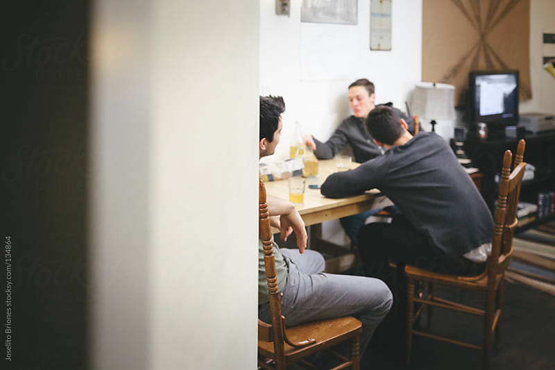 Mexican-American Young Men Friends and Roommates Talking in Dining Table by Joselito Briones for Stocksy United