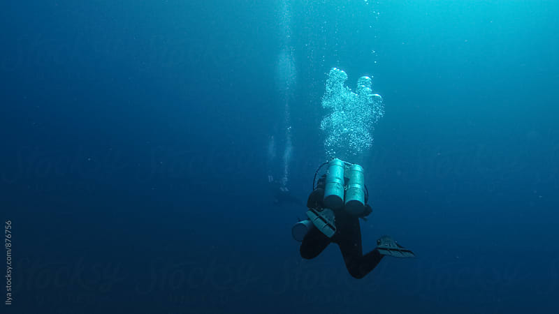 Group of scuba divers swimming in the deep water by Ilya for Stocksy United
