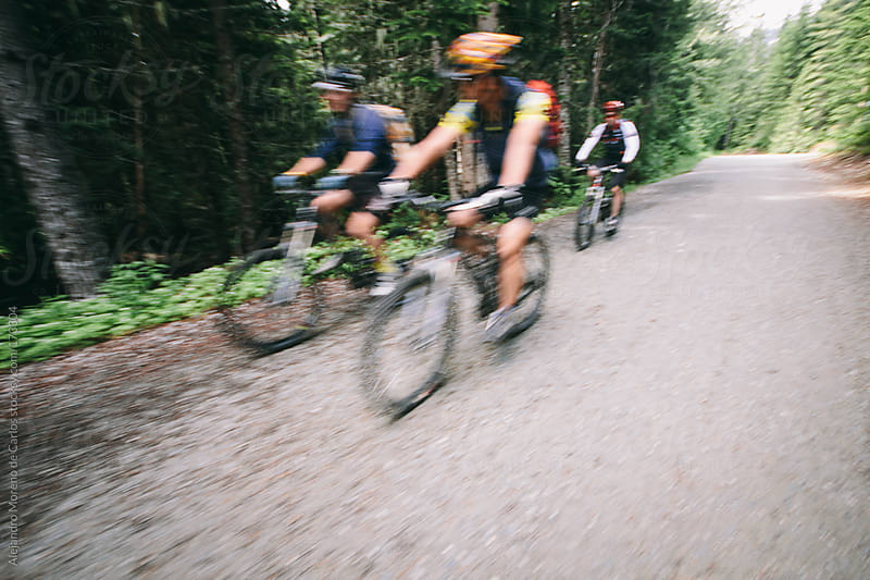 Cyclists riding bikes on path. Speed blurred image by Alejandro Moreno de Carlos for Stocksy United