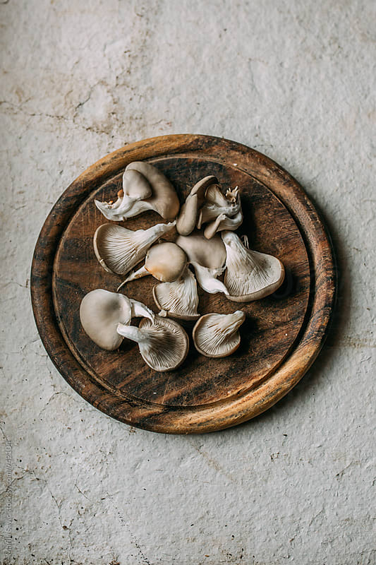 Oyster mushrooms on wooden board by Marija Savic for Stocksy United