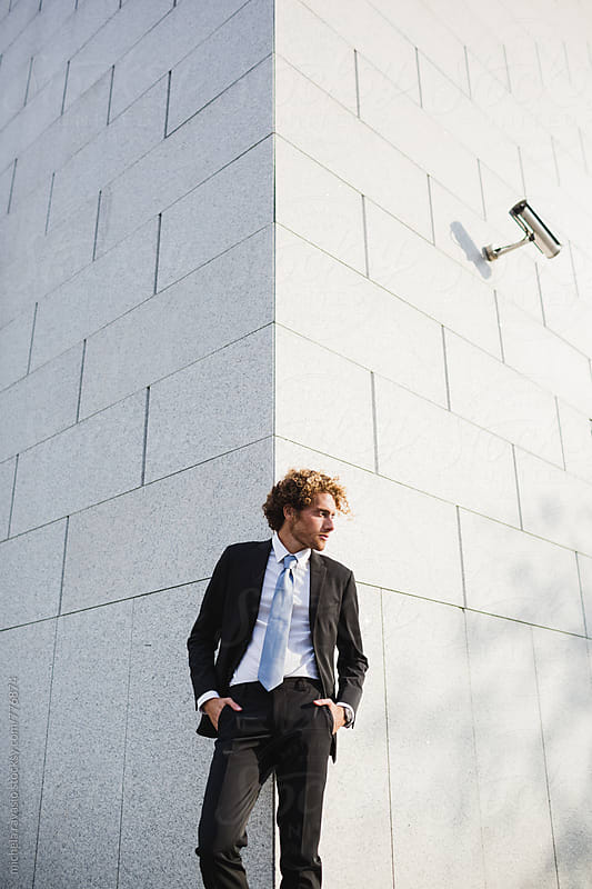 Man leaning against a wall with a surveillance camera above by michela ravasio for Stocksy United