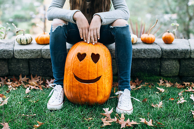 Teenage girl sitting with her large carved pumpkin for Halloween with hearts for eyes by Carolyn Lagattuta for Stocksy United