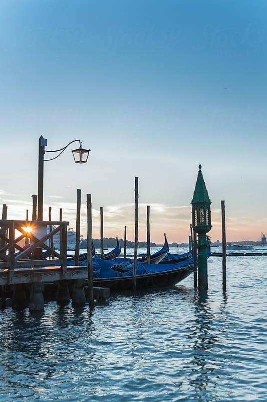 Venetian gondolas at sunrise by Leander Nardin for Stocksy United