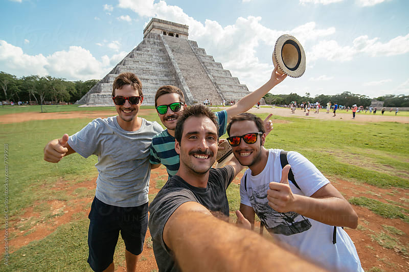 Young group of friends wearing sunglasses taking a selfie in front of Kukulkan pyramid in Chichen Itza, Mexico by Alejandro Moreno de Carlos for Stocksy United