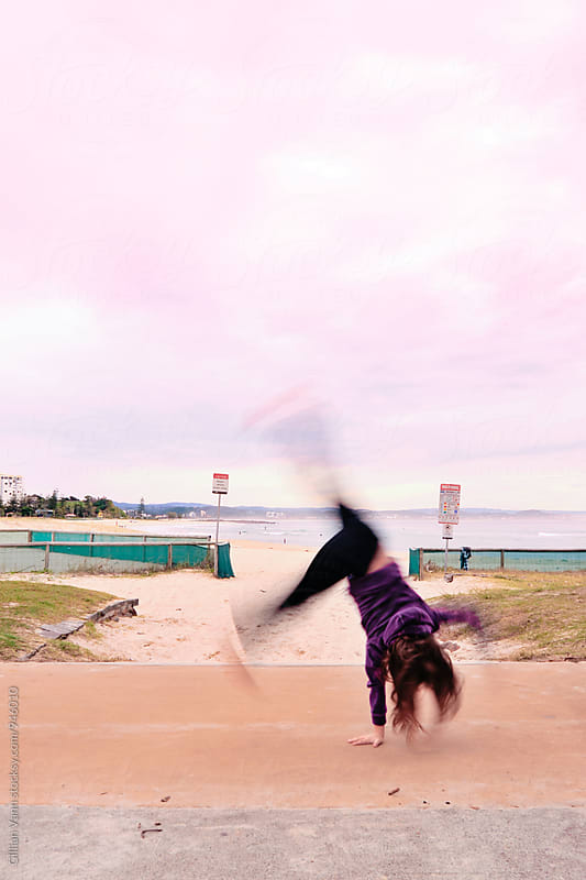 girl doing cartwheel at the beach in the pretty pink early morning light by Gillian Vann for Stocksy United