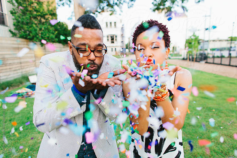 Hipsters blowing colorful confetti  by Kristen Curette Hines for Stocksy United