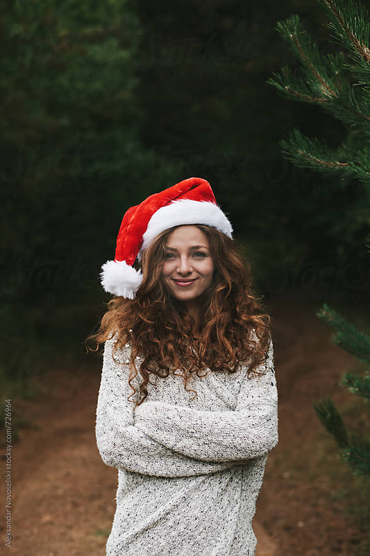 Beautiful young woman with christmas hat in the forest by Aleksandar Novoselski for Stocksy United