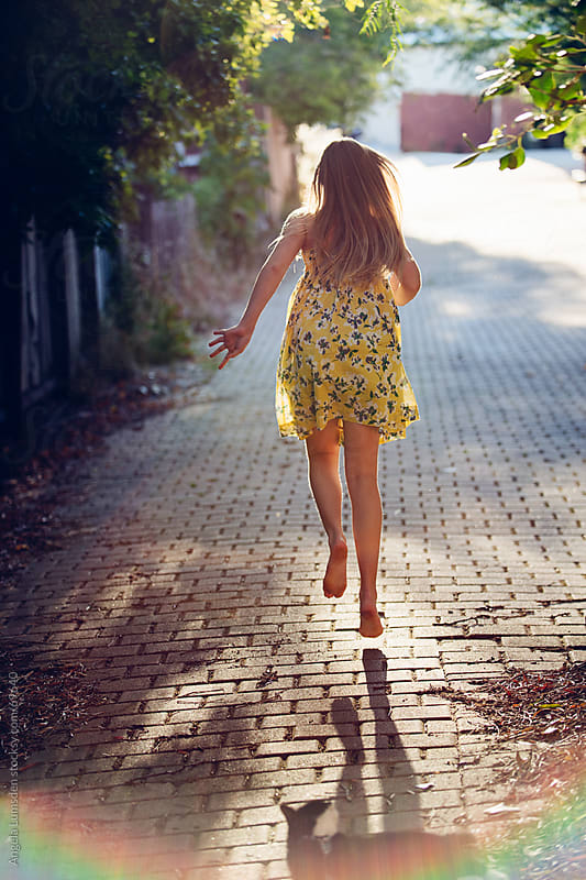 Girl running in a sundress by Angela Lumsden for Stocksy United