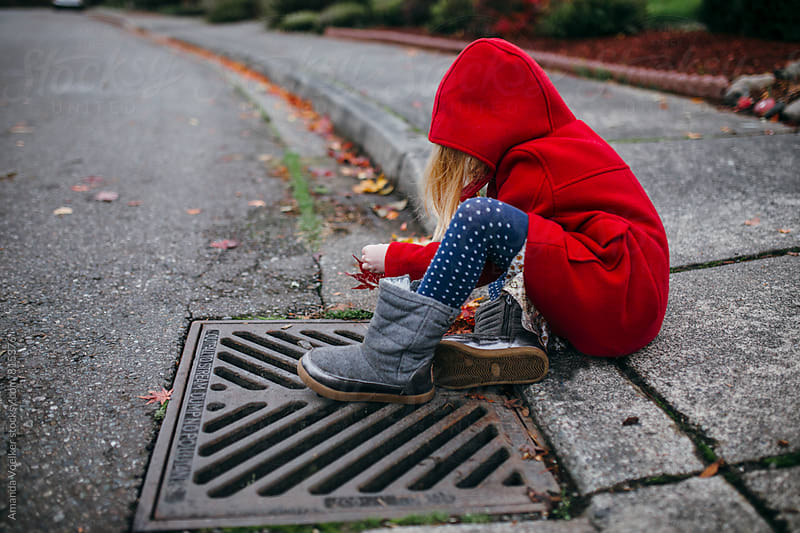 Little Girl Sits on the Sidewalk in A Bright Red Coat by Amanda Voelker for Stocksy United