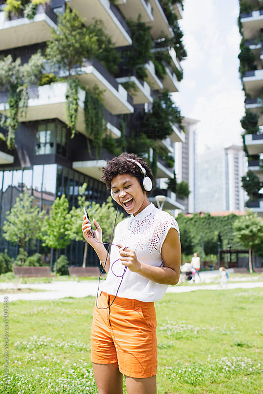 Young woman with headphones singing outdoors by michela ravasio for Stocksy United