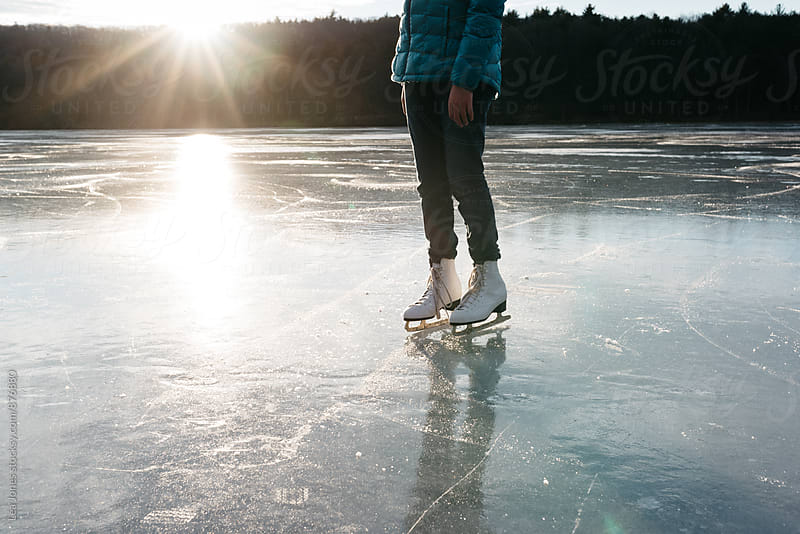 young woman standing on a frozen lake with skates by Léa Jones for Stocksy United