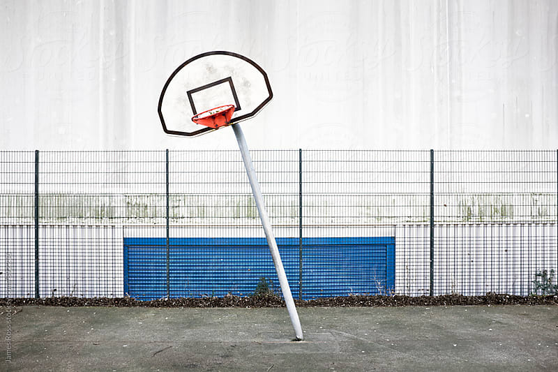 A bent basketball net on a court by James Ross for Stocksy United