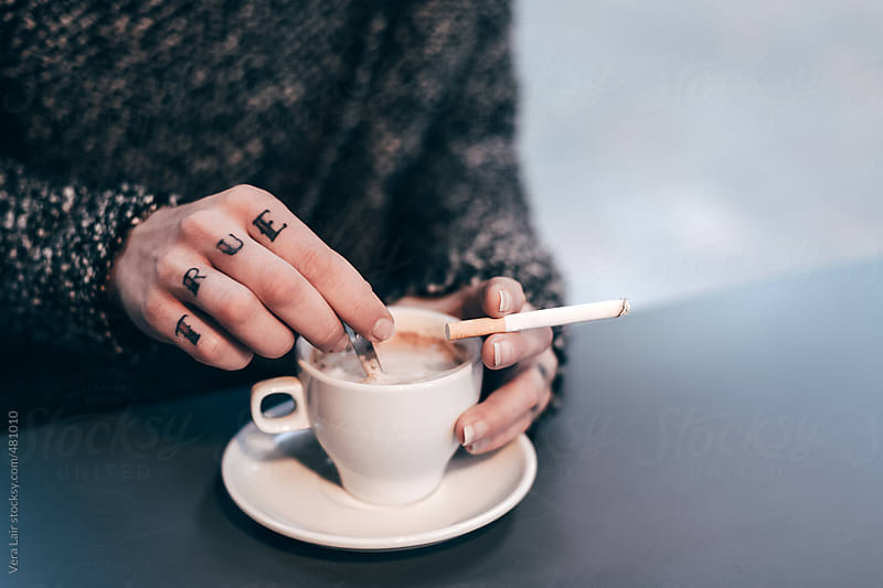 Woman hands with true tattoo and a cup of coffee by Vera Lair for Stocksy United