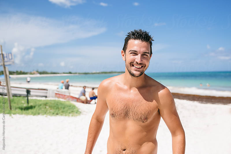 Young happy man smiling and having fun on tropical beach by Alejandro Moreno de Carlos for Stocksy United