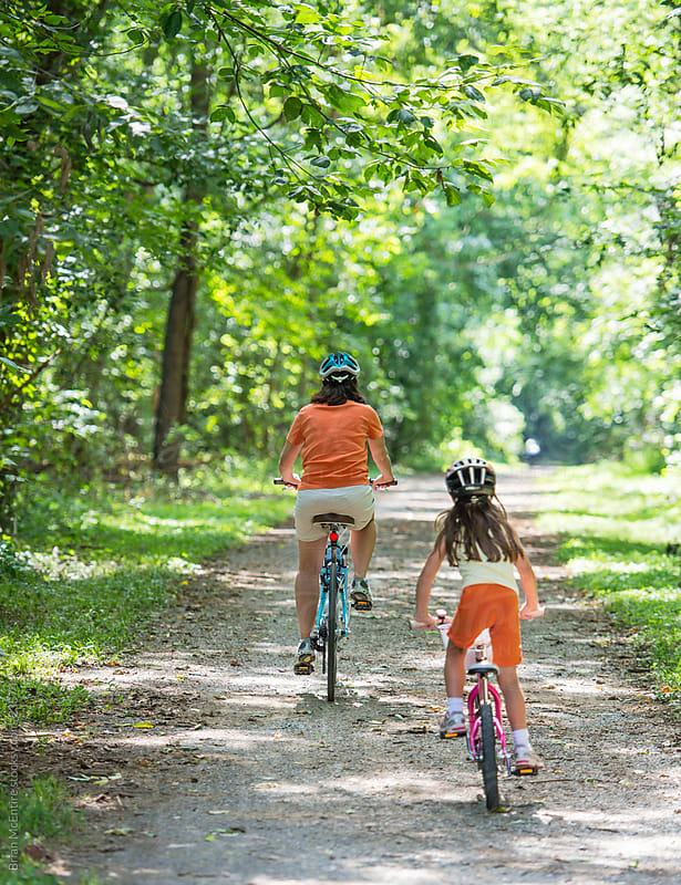 Family: Mother and Daughter Biking on Wooded Path by Brian McEntire for Stocksy United