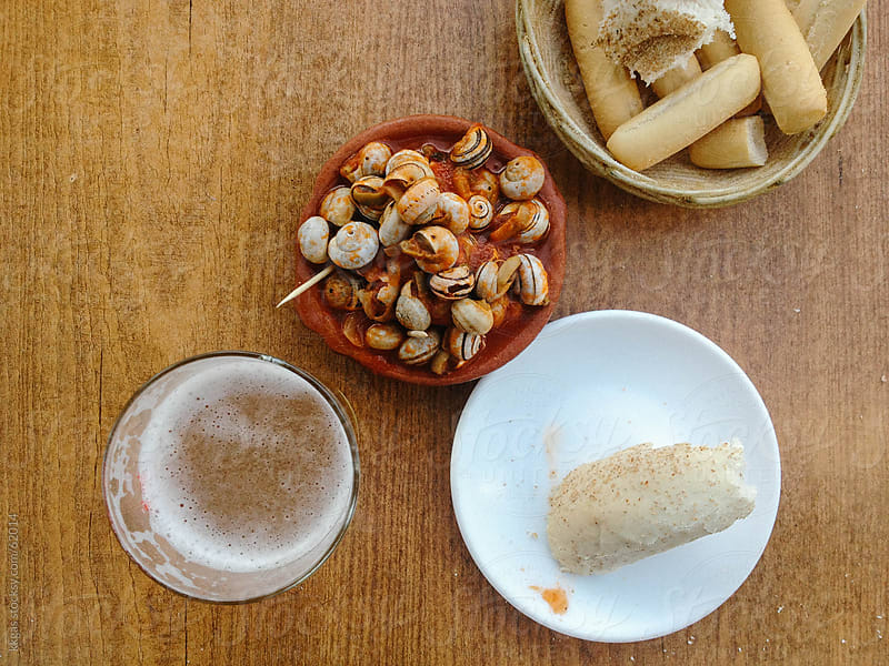 Snails in tomato sauce with bread and beer. by kkgas for Stocksy United