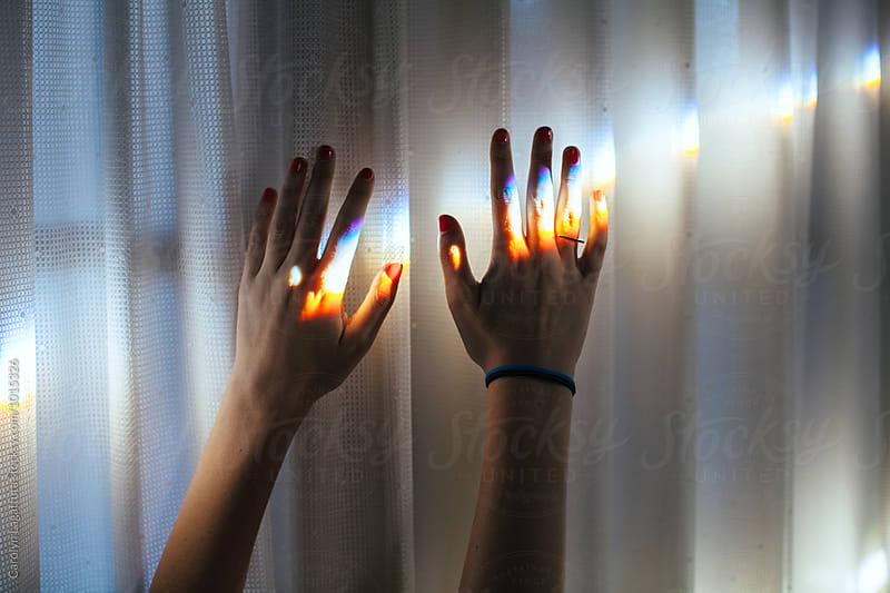 Two hands reaching toward the light by Carolyn Lagattuta for Stocksy United