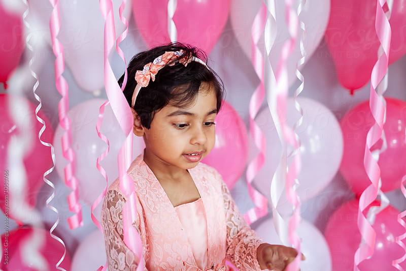 Cute little girl surrounded by birthday party streamers by Saptak Ganguly for Stocksy United