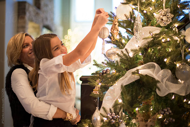 Little Girl and Mother Hang Christmas Decorations on Christmas Tree  by JP Danko for Stocksy United