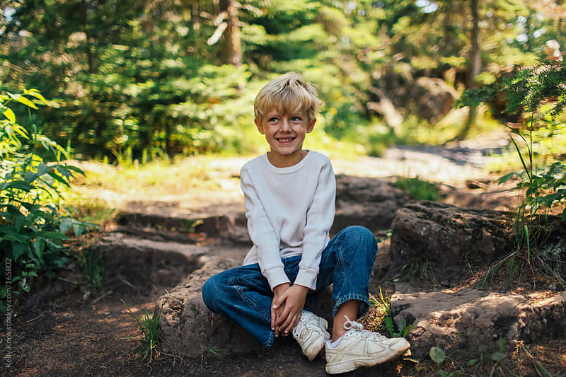 smiling boy rests on a rock by Kelly Knox for Stocksy United