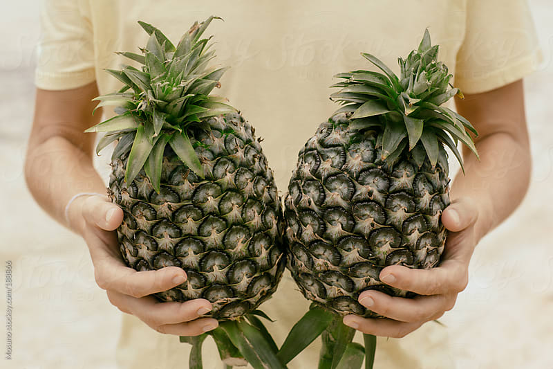 Anonymous Man Holding Two Pineapples by Mosuno for Stocksy United