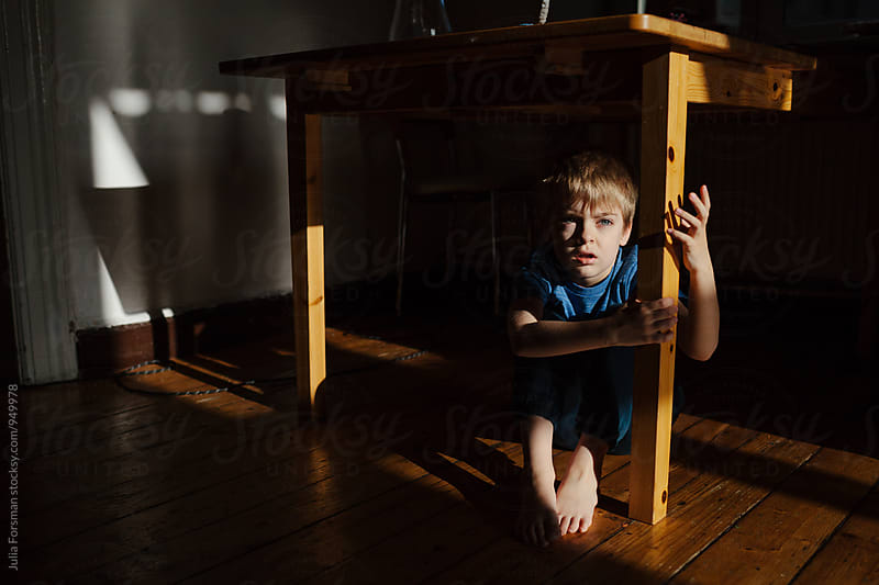 Little boy under a table. by Julia Forsman for Stocksy United