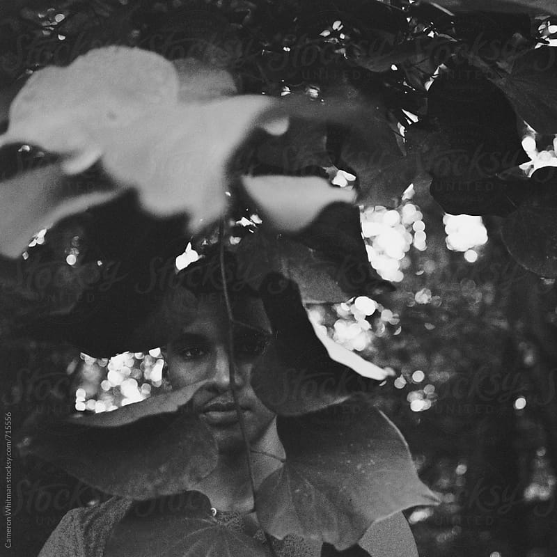 Obscurred by leaves- Nature portraits of a handsome young man by Cameron Whitman for Stocksy United