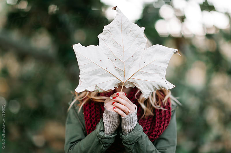 Woman holding a large leaf in front of her face by Kayla Snell for Stocksy United