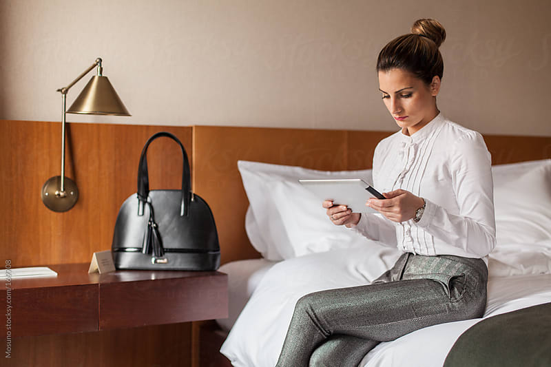 Businesswoman Using Technology in a Hotel Room by Mosuno for Stocksy United