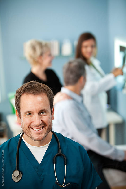 Exam Room: Male Nurse with Patients Behind by Sean Locke for Stocksy United