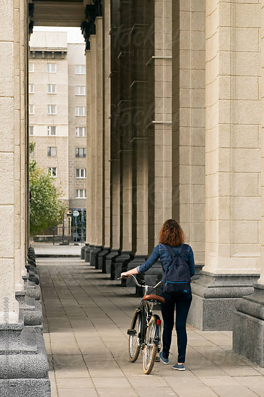 Brunette in denim with backpack walking with bike between columns by Danil Nevsky for Stocksy United