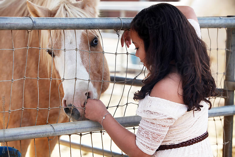 Brunette young girl petting a horse by Dina Giangregorio for Stocksy United