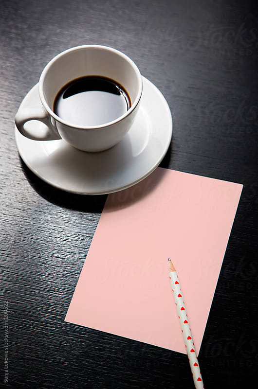 coffee, pink paper and pen on a black table by Sonja Lekovic for Stocksy United