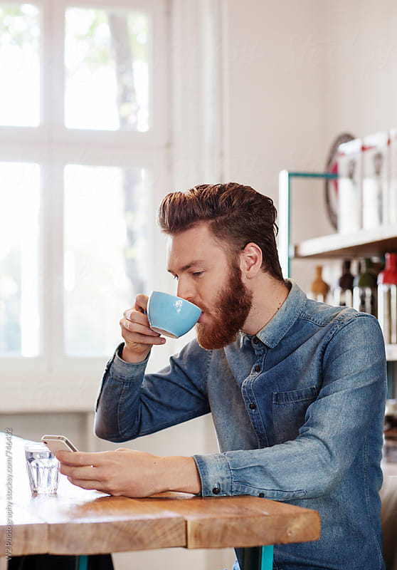 Young man with beard drinking coffee by W2 Photography for Stocksy United
