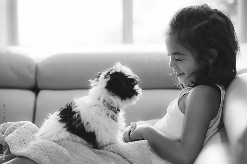 Little Girl With Little Puppy by Ronnie Comeau for Stocksy United