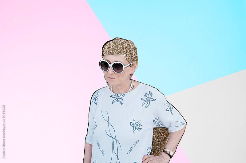 Minimalist concept of a mature woman cut out of paper and out on glitter and colorful background by Beatrix Boros for Stocksy United