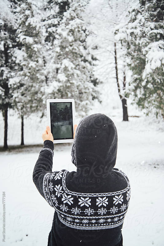 Woman taking a photo of snowy trees by Pixel Stories for Stocksy United