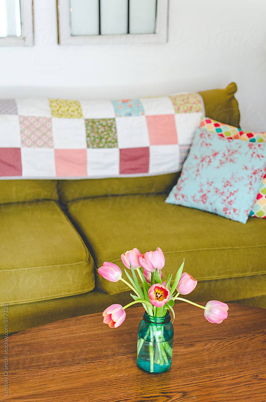 Tulips on a coffee table in a living room by Lindsay Crandall for Stocksy United
