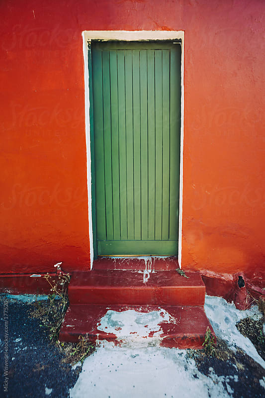 Green door red wall with spilt paint on the floor by Micky Wiswedel for Stocksy United