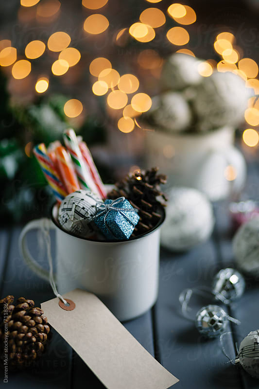 Christmas decoration and sweets on a table, with lights in background. by Darren Muir for Stocksy United