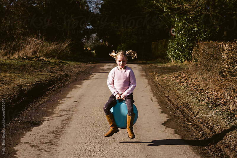 A little girl travelling along a country lane on a space hopper. by Helen Rushbrook for Stocksy United