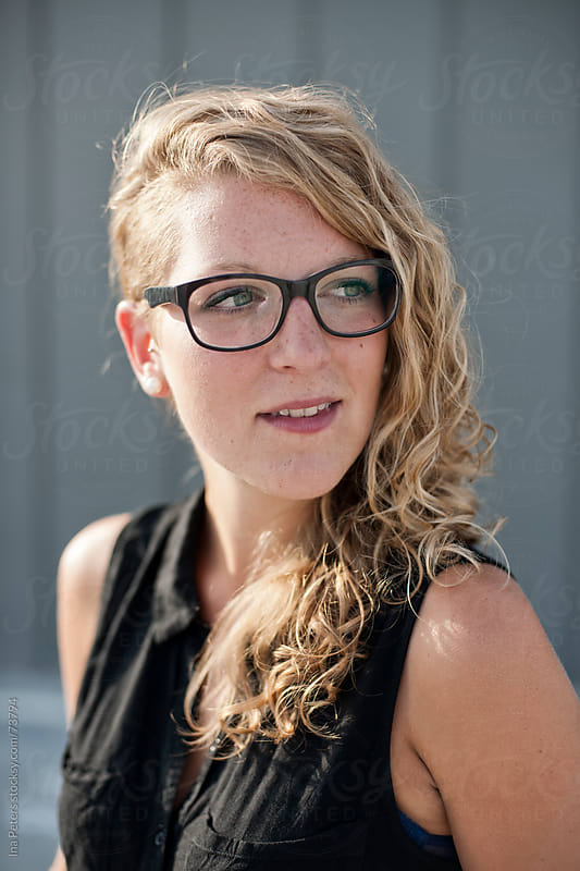 People: Portrait of a young beautiful woman with black glasses by Ina Peters for Stocksy United