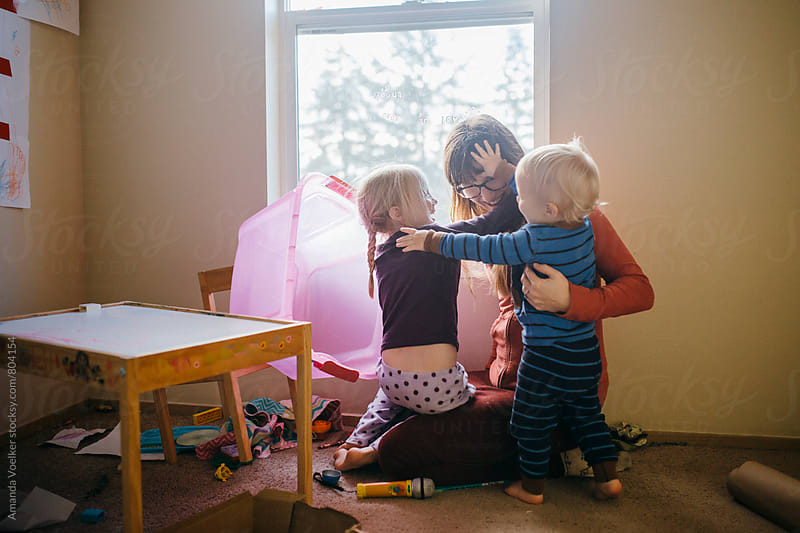 Mother and Children play and hug in a messy room by Amanda Voelker for Stocksy United