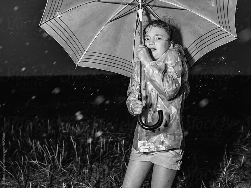 Young girl stuck in the rain during a storm by Robert Lang for Stocksy United