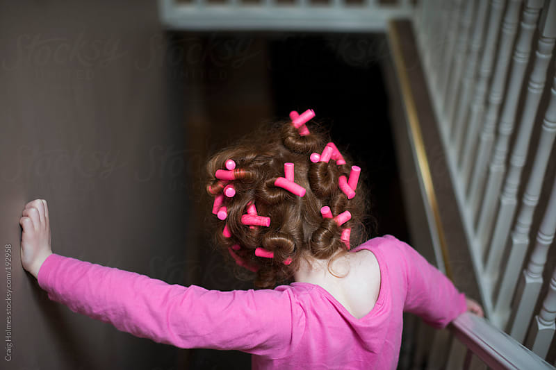 A little girl with bendy rollers in her hair by Craig Holmes for Stocksy United