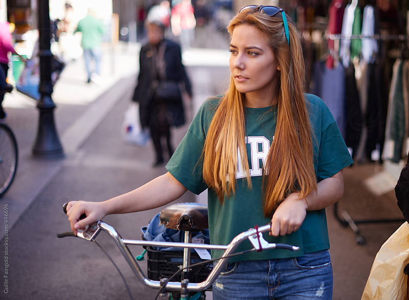 teenager walking with her cycle around the city by Guille Faingold for Stocksy United